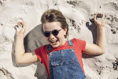 Südafrika, Westerncape, Kapstadt, Mädchen mit Sonnenbrille liegt im Sand, Urlaub - MCF00344