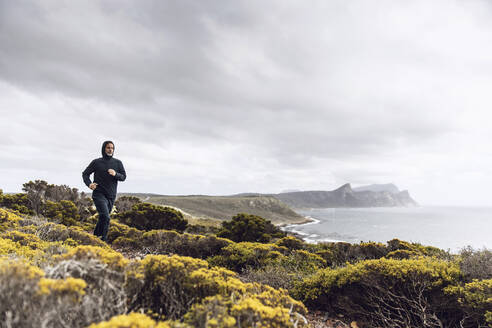 Man jogging in rural scene, Cape Point, Western Cape, South Africa - MCF00347