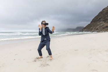 Businessman using VR glasses on the beach, Nordhoek, Western Cape, South Africa - MCF00353