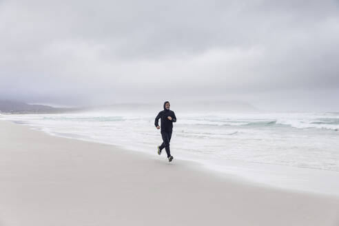 Man jogging on the beach, Nordhoek, Western Cape, South Africa - MCF00356
