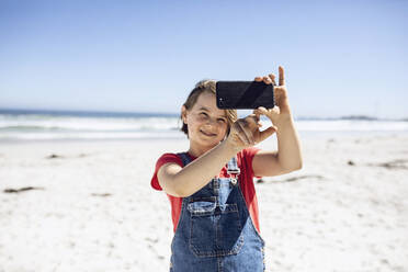 Girl taking selfie with smartphone on the beach, Cape Town, Western Cape, South Africa - MCF00362