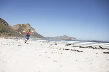 Girl listening music with headphones, dancing on the beach, Cape Town, Western Cape, South Africa - MCF00365