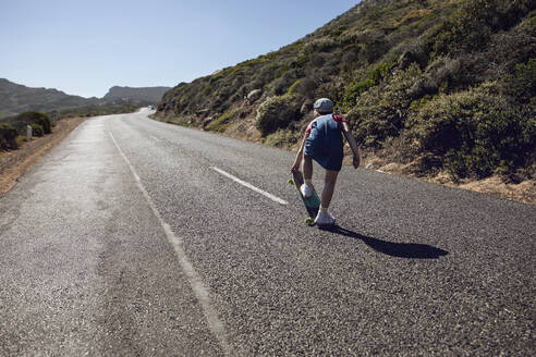 Back view of girl with skateboard standing on country road, Cape Town, Western Cape, South Africa - MCF00374