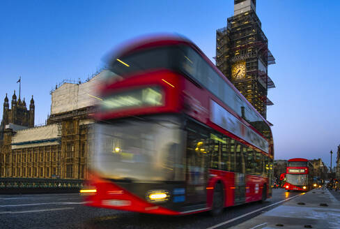UK, England, London, Double-decker bus driving past Palace of Westminster at dawn - LOMF00915