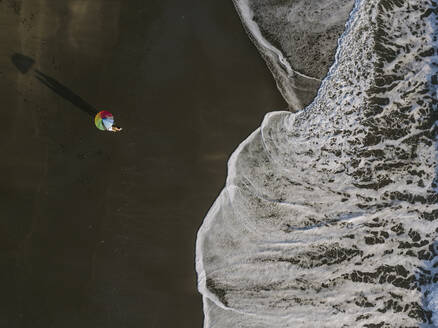 Aerial view of couple unde rainbow colors umbrella at the beach, Kedungu beach, Bali, Indonesia - KNTF03730