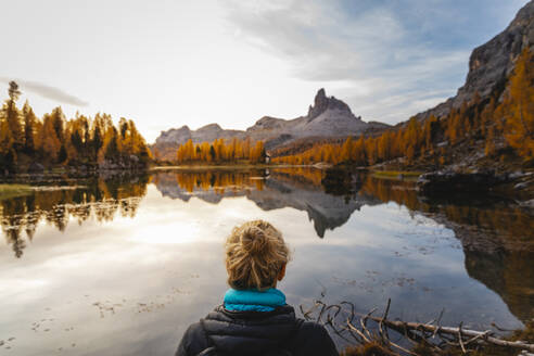 Female hiker looking at the mountain landscape with lake at the first light of the day, Dolomites Alps, Cortina, Italy - MRAF00440