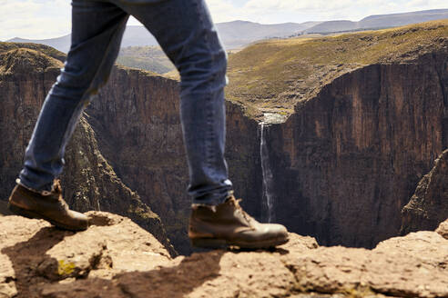 Low section of a man walking through the mountains, Maletsunyane Falls, Lesotho - VEGF00841