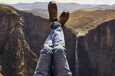 Low section of a man with legs up in the mountains, Maletsunyane Falls, Lesotho - VEGF00844
