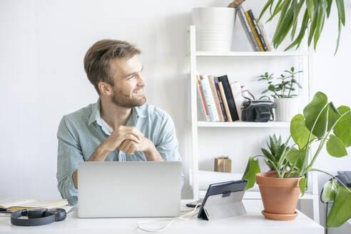 Smiling man at desk in office looking sideways - VPIF01756