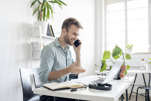 Smiling man on the phone at desk in office - VPIF01759