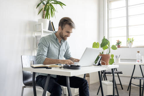 Smiling man using laptop at desk in office - VPIF01762