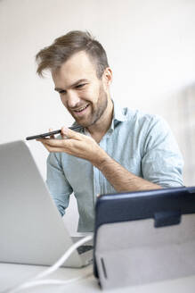 Smiling man using smartphone at desk in office - VPIF01765