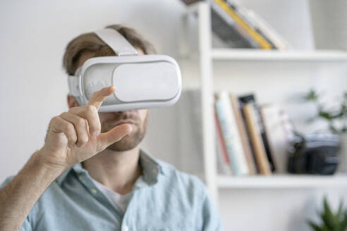 Portrait of man wearing VR glasses in office - VPIF01774