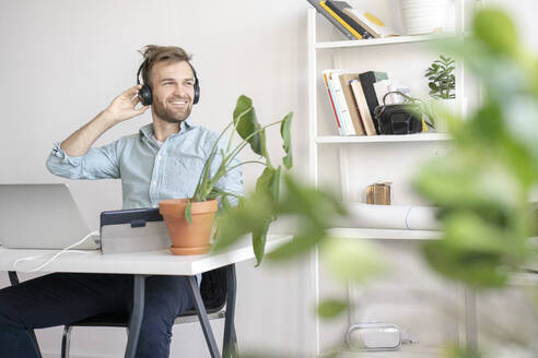 Smiling man listening to music at desk in office - VPIF01777