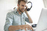 Smiling man with headphones and laptop at desk in office - VPIF01780