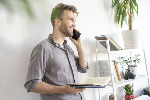 Smiling man on the phone in office - VPIF01786