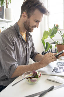 Smiling man using smartphone during lunch break at desk in office - VPIF01801