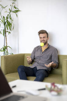 Smiling man sitting on couch in office playing with a tennis ball - VPIF01804