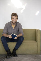 Portrait of smiling man sitting on couch with a book - VPIF01807