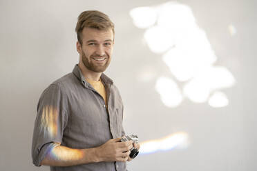 Portrait of smiling man holding old-fashioned camera - VPIF01810