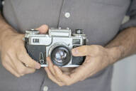 Close-up of man holding old-fashioned camera - VPIF01813