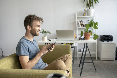 Smiling man sitting on couch in office using tablet - VPIF01816