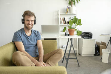Portrait of smiling man sitting on couch in office listening to music - VPIF01819