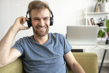 Portrait of smiling man sitting on couch in office listening to music - VPIF01822