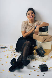 Portrait of young woman dressed for a party, celebrating Christmas with gifts and champagne - MPPF00305