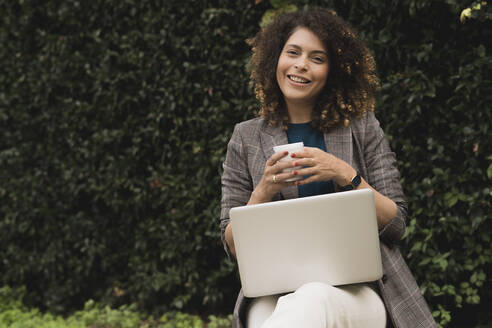 Portrait of smiling woman with coffee and laptop outdoors - FMOF00772