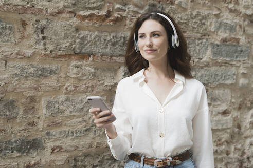 Young woman with smartphone and headphones outdoors at a stone wall - FMOF00796