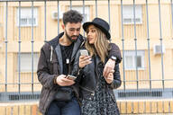 Young couple in the city using their mobile phones - ERRF02166