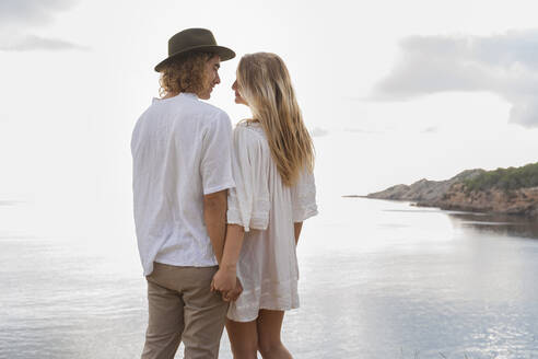Young couple in love standing in front of the sea holding hands, Ibiza, Balearic Islands, Spain - AFVF04254