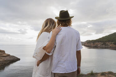 Back view of young couple in front of the sea looking at view, Ibiza, Balearic Islands, Spain - AFVF04260