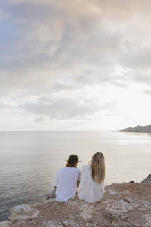 Back view of young couple sitting on rock in front of the sea, Ibiza, Balearic Islands, Spain - AFVF04272