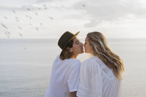 Young couple kissing in front of the sea, Ibiza, Balearic Islands, Spain - AFVF04275