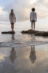 Back view of young couple standing on rocks in front of the sea, Ibiza, Balearic Islands, Spain - AFVF04278