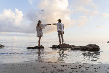 Young couple standing on rocks in front of the sea holding hands, Ibiza, Balearic Islands, Spain - AFVF04281