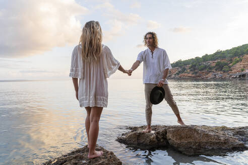 Young couple standing on rocks in front of the sea holding hands, Ibiza, Balearic Islands, Spain - AFVF04284