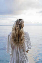 Back view of young blond woman  standing in front of the sea, Ibiza, Balearic Islands, Spain - AFVF04287