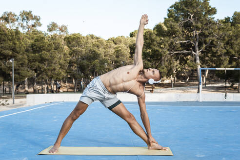 Barechested muscular man practicing fitness exercises outdoors - RCPF00128