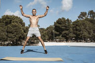 Portrait of barechested muscular man practicing fitness exercises outdoors - RCPF00131