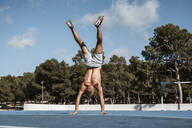 Barechested muscular man doing a handstand outdoors - RCPF00134