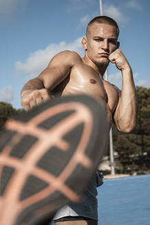 Portrait of barechested muscular man practicing fitness exercises outdoors - RCPF00137