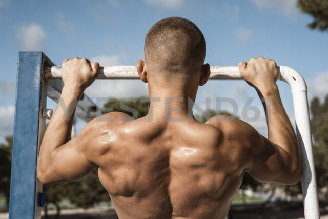 Rear view of barechested muscular man practicing fitness exercises on football goal outdoors - RCPF00140 - Rafa Cortés/Westend61