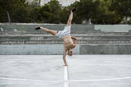 Barechested muscular man doing a handstand on one arm outdoors - RCPF00152