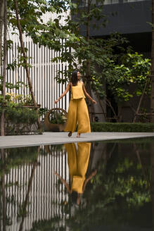 Fashionable woman dressed in yellow dancing in the city - MAUF03126