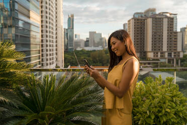 Smiling woman standing on roof terrace looking at smartphone, Bangkok, Thailand - MAUF03138