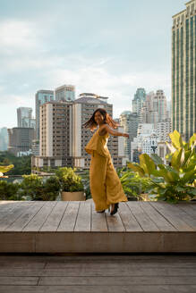 Happy woman dancing on roof terrace, Bangkok, Thailand - MAUF03141
