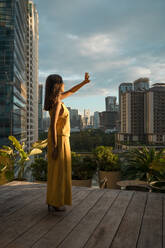 Woman standing on roof terrace at sunlight, Bangkok, Thailand - MAUF03144